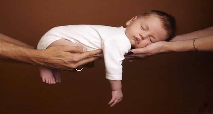 bebé aguantado por manos